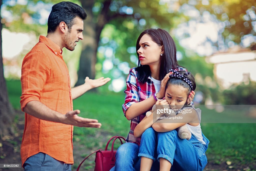 Husband is arguing with wife at the front of their little daughter : Stock Photo