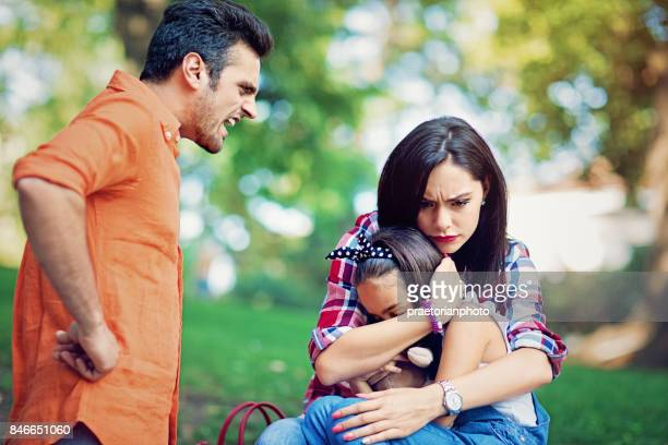 Husband is arguing with wife at the front of their little daughter