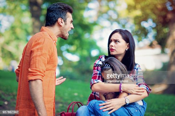 husband is arguing with wife at the front of their little daughter - guarding stock photos and pictures