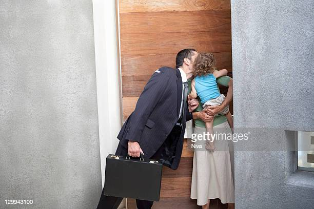 Husband kissing wife before work