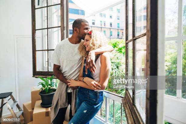 husband kissing wife on forehead while standing by window in new house - forehead stock pictures, royalty-free photos & images