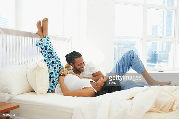 Husband laughing with pregnant wife in bed