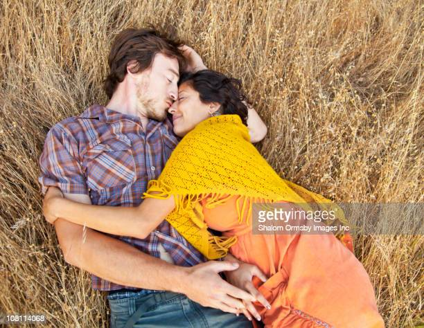 Husband laying with pregnant wife in dry grass
