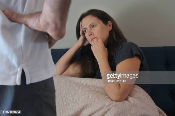 husband looking at his sad depressed wife - rafael ben ari stock pictures, royalty-free photos & images