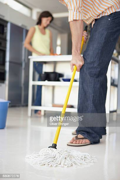 Husband mopping, wive in background