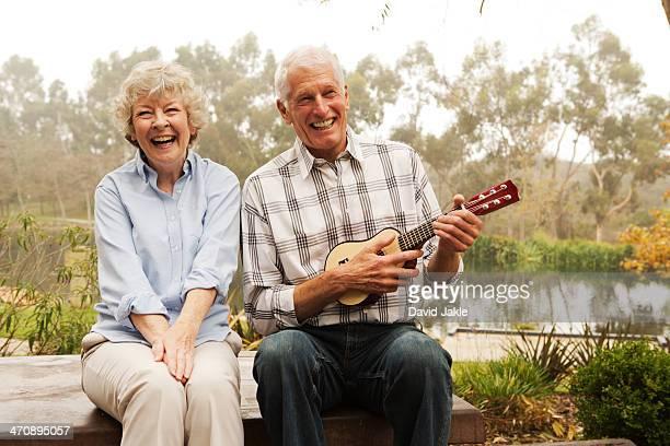 Husband playing the ukulele with wife by lake
