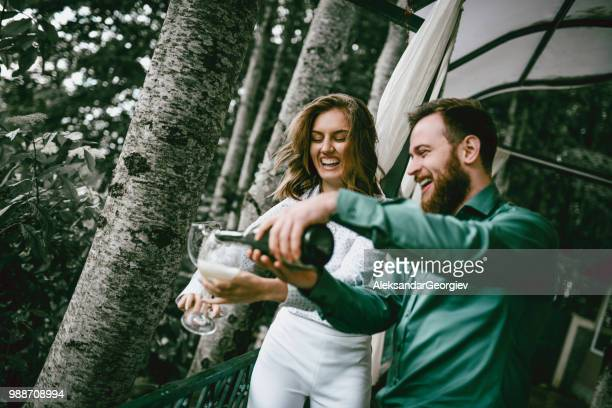 husband pouring champagne into glasses for him and his wife's anniversary - drunk wife at party stock pictures, royalty-free photos & images