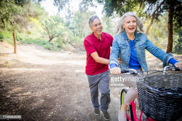 husband pushing wife on bicycle - chasing stock pictures, royalty-free photos & images
