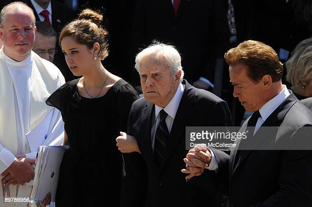 Husband Sargent Shriver is helped by California Gov Arnold Schwarzenegger out of St Xavier Church after Eunice Kennedy Shriver's funeral August 14...