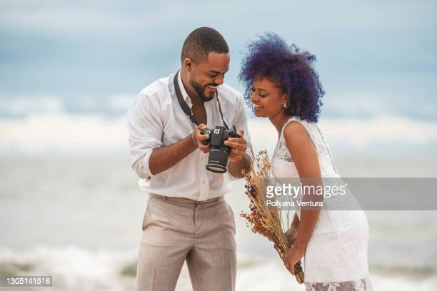 husband shows wedding photos to wife - fiancé stock pictures, royalty-free photos & images