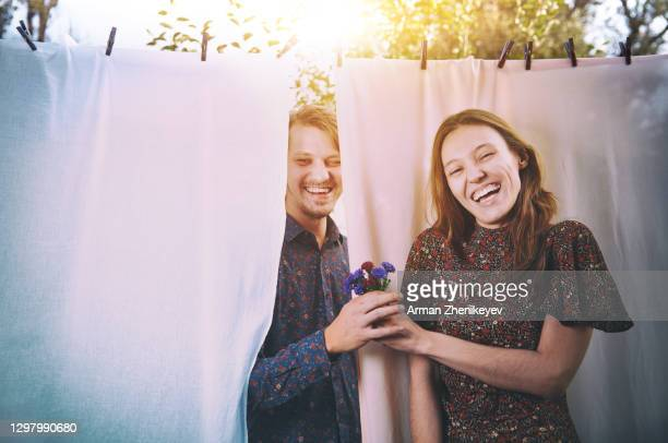 husband surprised his wife with flowers against laundry hanging on clothesline - simple living stock pictures, royalty-free photos & images