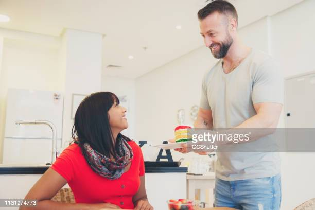 夫は、ケーキのマルチカラースライスで妻を驚かせる - 1周年 ストックフォトと画像