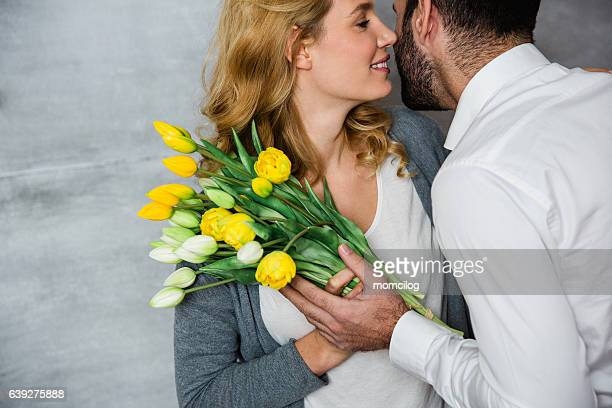 Husband surprising his wife with flowers