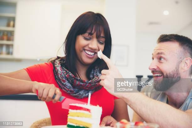 妻は誕生日ケーキをカットしながら、夫は彼の妻をからかう - 1周年 ストックフォトと画像