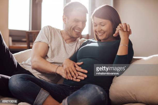 husband touching wife's stomach - pregnant stock pictures, royalty-free photos & images
