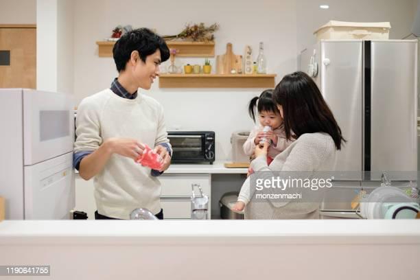 夫は妊娠中の妻と台所で皿洗い - 夫 ストックフォトと画像
