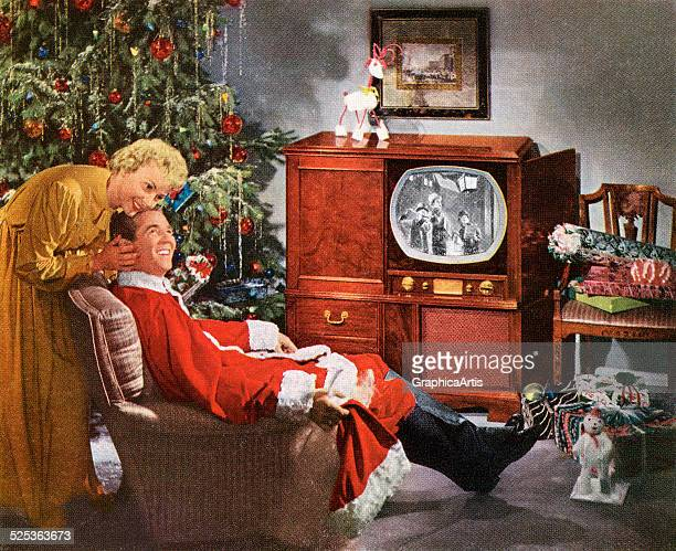 A husband wearing a Santa Claus suit watching television on Christmas Eve with his happy wife photograph 1950