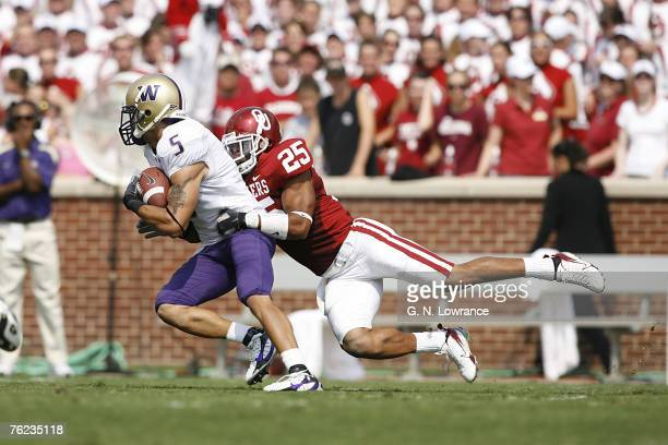Huskies receiver Anthony Russo is tackled by DJ Wolfe of Oklahoma during action between the Washington Huskies and Oklahoma Sooners at Owen Field in...