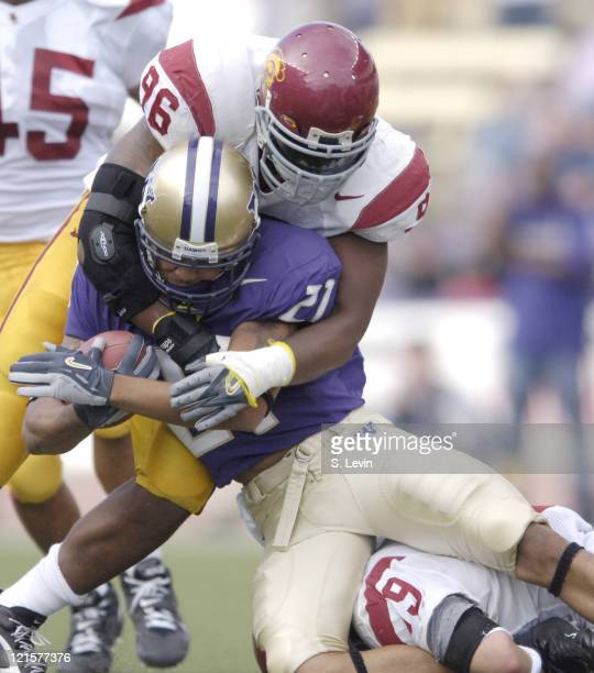 Huskies Sonny Shackelford is taken down by Trojans Lawrence Jackson during the game between the USC Trojans and the University of Washington Huskies...