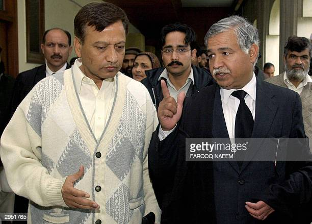 Hussamul Haq brother of Major Islam ulHaq the senior aide to the father of Pakistan's nuclear bomb speaks with his lawyer Ikram Chaudhary after a...