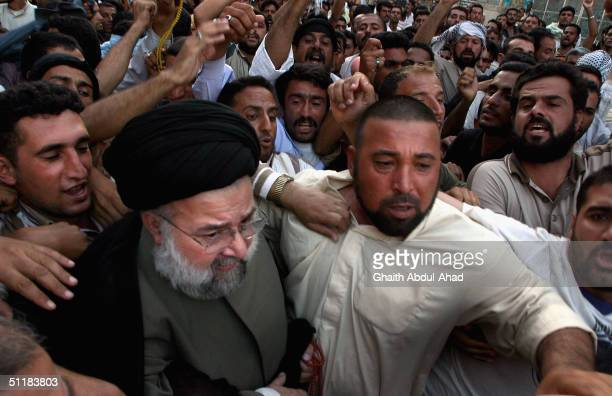 Hussein al-Sadr, , the head of a delegation of members of the Iraqi National Conference, is surrounded by crowds, chanting for Moqtada Sadr, as he...