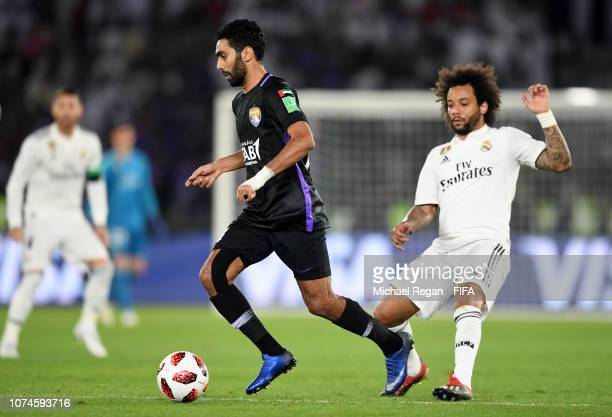 Hussein El Shahat of Al Ain runs with the ball under pressure from Marcelo of Real Madrid during the FIFA Club World Cup UAE 2018 Final between Al...