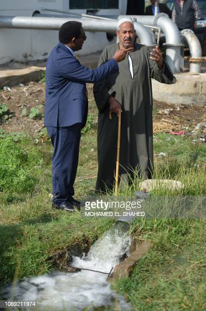 Hussein Gadain UN's Food and Agriculture Organization representative inspects with a farmer the water pump in Kafr alDawar village in northern...
