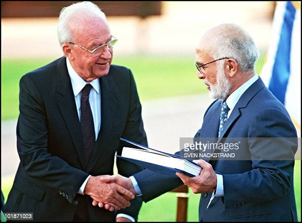 Hussein Ibn Talal, King of Jordan and Israeli Premier Yitzhak Rabin shake hands after they exchanged the documents of the Peace Treaty at Beit...