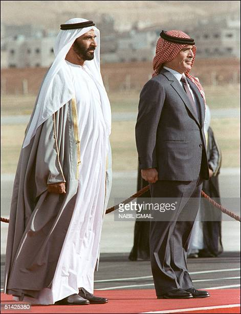 Hussein Ibn Talal King of Jordan and President Sheikh Zayed bin Sultan alNahyan of the United Arab Emirates listen to national anthems at Marka...