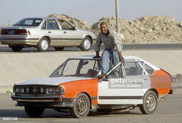 'IRAQLIFESTYLEYOUTHMOTORING' Hussein Madrud performs a stunt in his old taxi in front of friends as they gather in a Baghdad car park 04 June 2004...