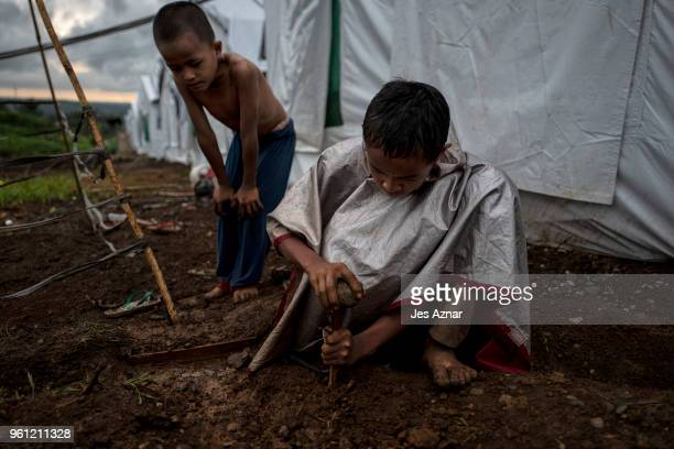 Hussein Romoros and his brother Yasser building a small garden plot outside their tent shelter inside Sarimanok tent city on May 15 2018 in Marawi...
