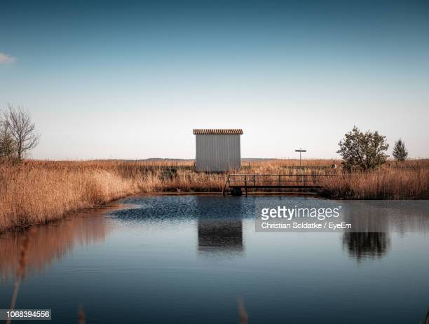 hut by pond against clear sky - christian soldatke stock pictures, royalty-free photos & images