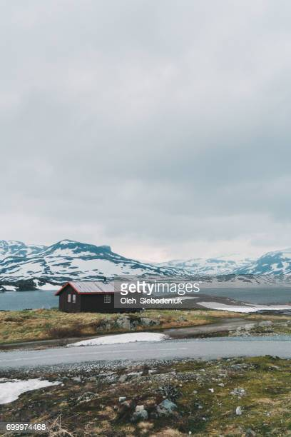 hut near the  lake in snowcapped mountains in norway - hut stock pictures, royalty-free photos & images