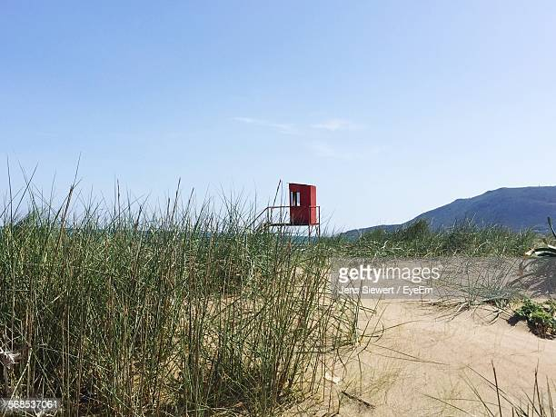 hut on grassy beach against sky - jens siewert stock-fotos und bilder