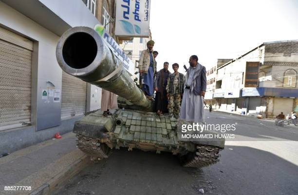 Huthi rebel fighters are pictured atop a tank in front of the residence of Yemen's former President Ali Abdullah Saleh in Sanaa on December 4 2017...