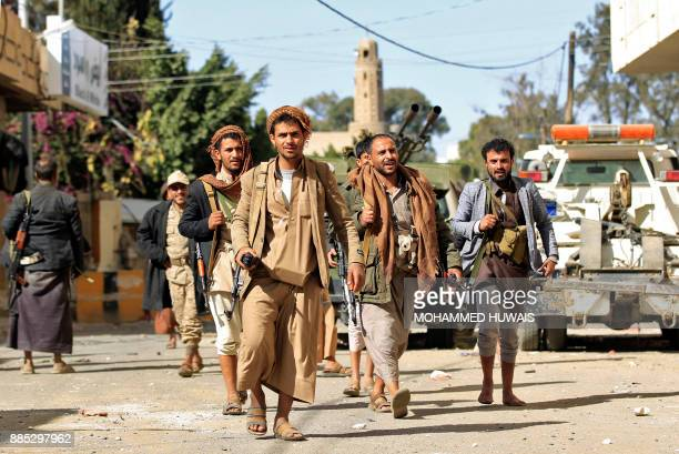Huthi rebel fighters are seen outside of the residence of Yemen's former President Ali Abdullah Saleh in Sanaa on December 4 2017 Yemen's...