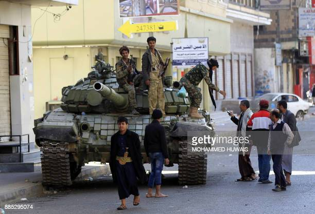 Huthi rebel fighters are seen riding a tank outside of the residence of Yemen's former President Ali Abdullah Saleh in Sanaa on December 4 2017...