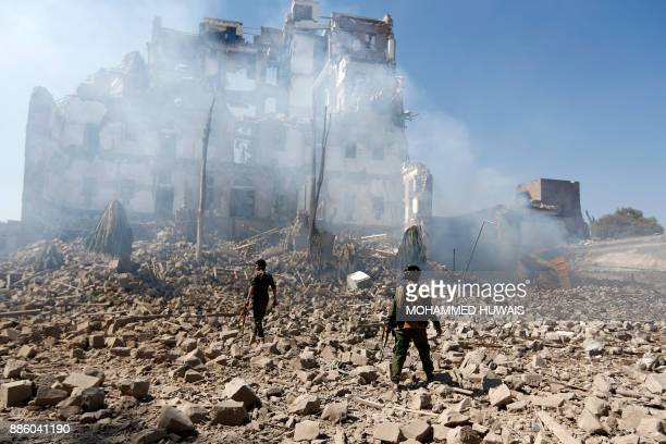 Huthi rebel fighters inspect the damage after a reported air strike carried out by the Saudi-led coalition targeted the presidential palace in the...