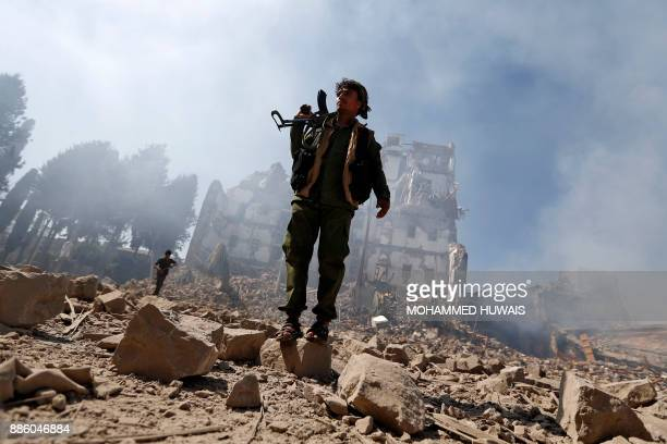TOPSHOT Huthi rebel fighters inspect the damage after a reported air strike carried out by the Saudiled coalition targeted the presidential palace in...