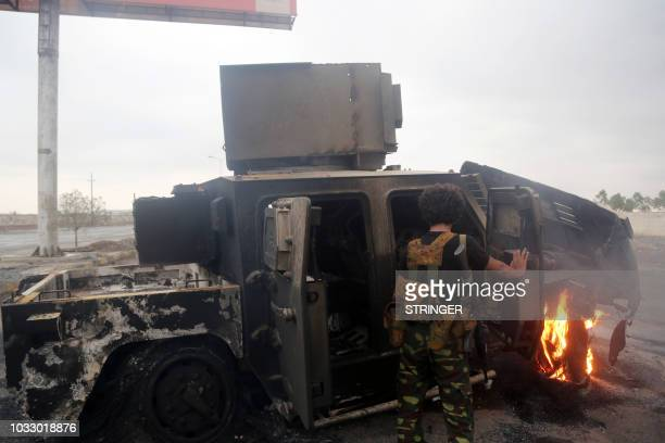 A Huthi rebel inspects a burnt armoured vehicle on September 13 reportedly destroyed in an air strike during clashes between fighters loyal to...