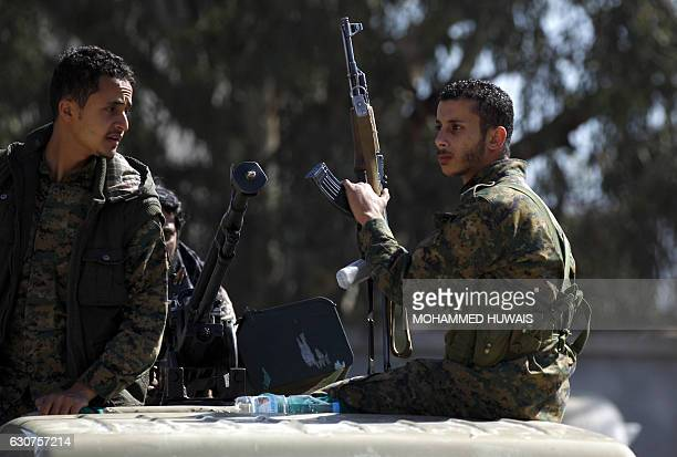 Huthi rebels dressed in army fatigues stand guard during a gathering in the capital Sanaa to mobilize more fighters to battlefronts to fight...