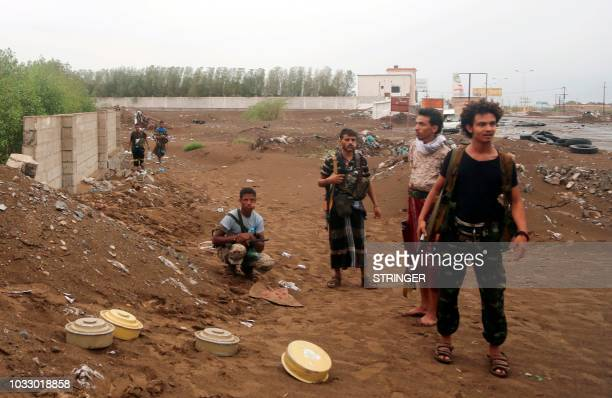 Huthi rebels stand near landmines that have been removed in the city of Hodeidah on September 13 as coalition forces seized rebel supply routes into...