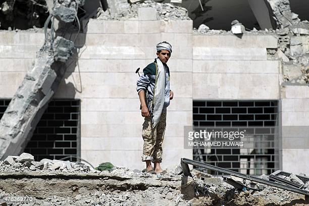 Huthi Shiite militant inspects what remains of a hotel destroyed in an air-strike by the Saudi-led coalition on May 31, 2015 in Al-Thawra sport city...