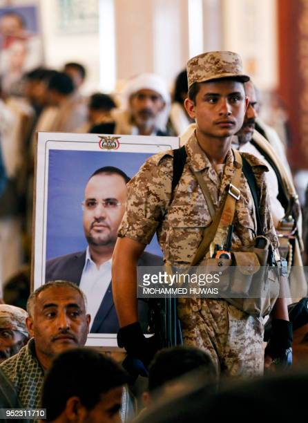 A Huthi soldier stands guard as mourners raise the portrait of slain Huthi leader Saleh alSamad and his six body guards during his funeral at a...