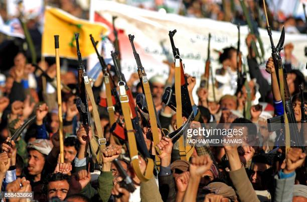 Huthi supporters brandish their weapons during a protest against US President Donald Trump's decision to recognize Jerusalem as the capital of Israel...