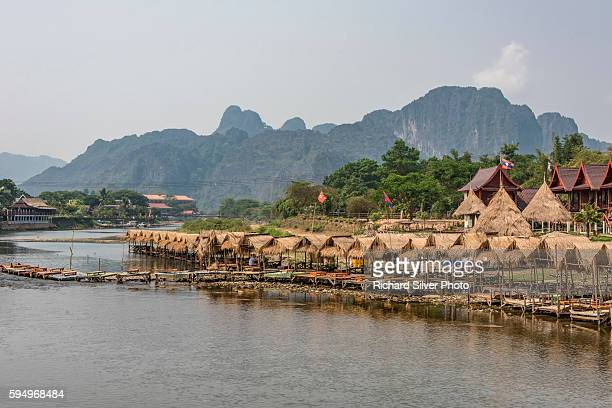 Huts dovering boats on the river side in Vang Vieng, Laos