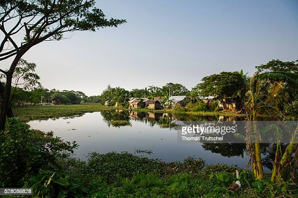 Huts of a slum are placed next to the Mayur River on April 11 2016 in Khulna Bangladesh