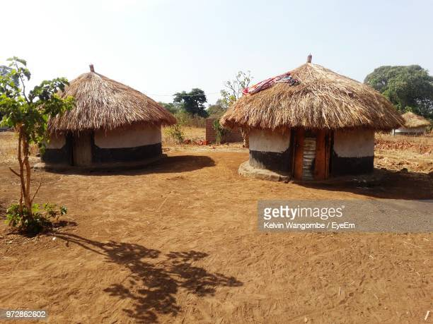 huts on field during sunny day - hut stock pictures, royalty-free photos & images