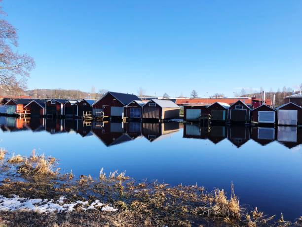 Huts Reflecting On Calm Lake Against Clear Blue Sky
