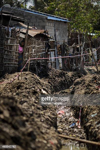 Huts stand next to a sewer on the edge of a slum on September 28 2015 in Beira Mozambique